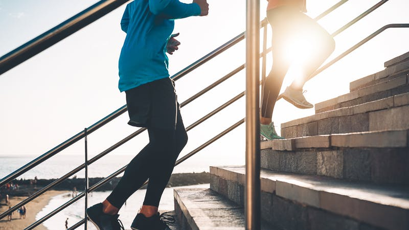 Vista de las piernas de los corredores entrenando al aire libre - Pareja joven haciendo una sesión de entrenamiento en las escaleras junto a la playa al atardecer - Gente sana, trotar y concepto de estilo de vida deportivo