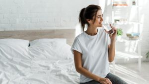 hermosa niña feliz sosteniendo agua potable de vidrio en la mañana