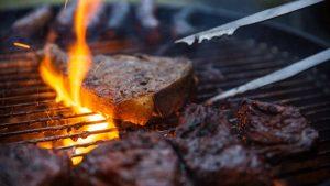Filetes a la parrilla a la llama se voltean en barbacoa con pinzas