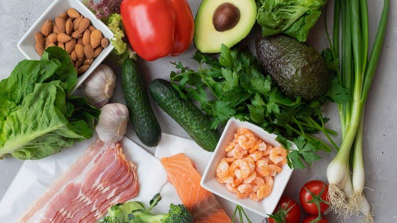 Concepto de dieta cetogénica.  Un conjunto de productos de nutrición cetogénica.  Verduras frescas, mariscos, tocino y nueces.