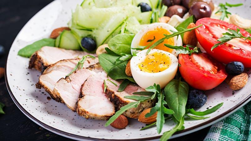 Dieta cetogénica.  Brunch cetogénico.  Huevo cocido, solomillo de cerdo y aceitunas, pepino, espinaca, queso brie, frutos secos y tomate.