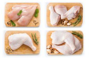 Maqueta de pollo y cerdo crudos en la tabla de cortar.  aislado